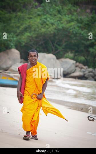 BUDDHIST MONK WALKING ALONG UNAWATUNA BEACH - Stock Image
