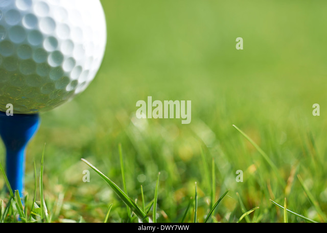 Close-up of golf ball resting on blue tee with grass and space for copy - Stock-Bilder
