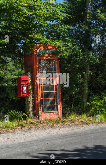 Old red phone box and red letter posting box on a country / rural road in Cornwall, UK. Box and telegraph pole to - Stock Image