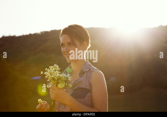 Young woman in meadow with bunch of wild flowers - Stock Image