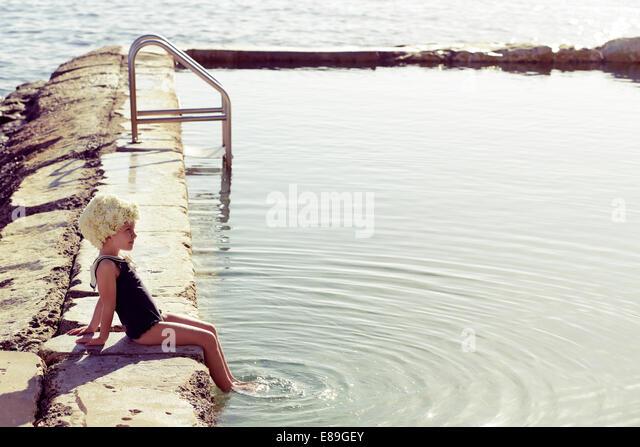 Girl in Flower cap sitting along pool - Stock Image