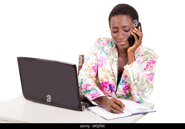 Young happy business woman working on a laptop by calling on mobile phone - Stock Image