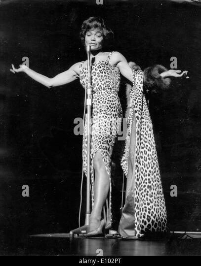 Singer Eartha Kitt performs in leopard print - Stock Image