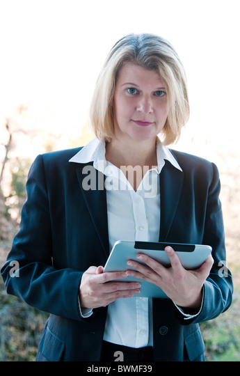 Middle aged busines woman standing in the doorway and holding her touchscreen tablet - Stock Image