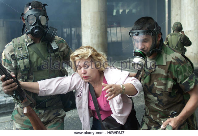 A woman is helped to safety in Caracas January 8, 2003. Venezuelan bank  worker's unions announced a 48-hour - Stock Image