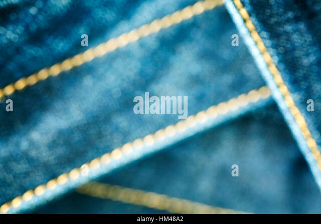 Blurred close up picture of blue jeans fabric with stitch, abstract background. - Stock Image