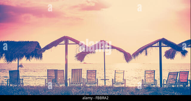 Vintage toned beach chairs and umbrellas at sunset, holidays background. - Stock-Bilder