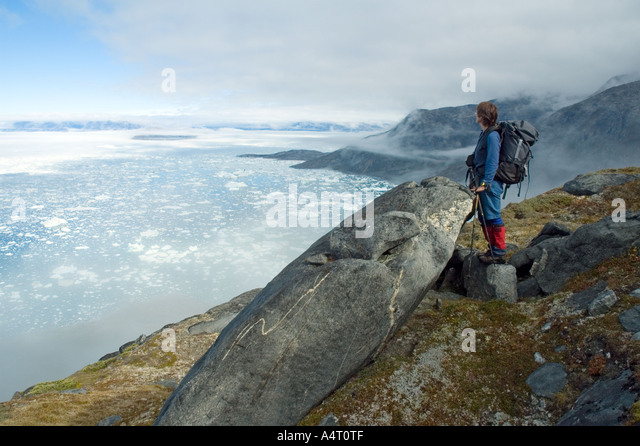 Trekker above Sermilik Fjord, East Greenland - Stock Image