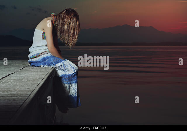 Lone woman in sad position over lake waters . Red dusk light - Stock-Bilder