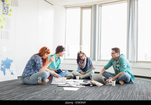 Businesspeople working on floor at creative work space - Stock Image