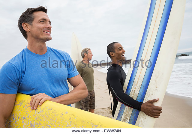 Men with surfboards on beach looking at ocean - Stock Image
