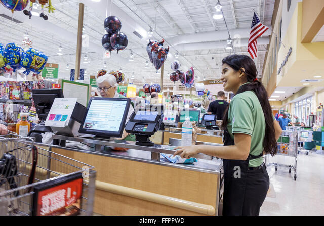 Ocala Florida Publix grocery store supermarket checkout cashier bagger Hispanic teen girl employee smiling - Stock Image