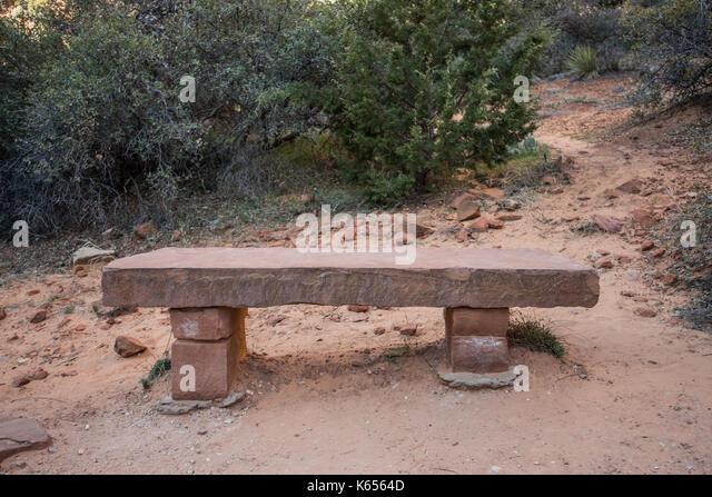 Stone Bench Along Desert Trail with scrub bush behind it - Stock Image