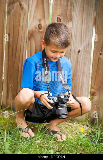 boy looking at his camera - Stock Image