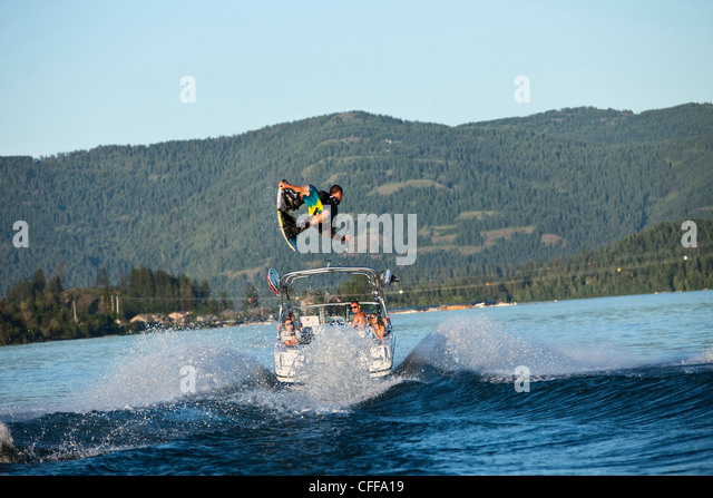 A professional wakeboarder jumps the wake on a lake in Idaho. - Stock Image