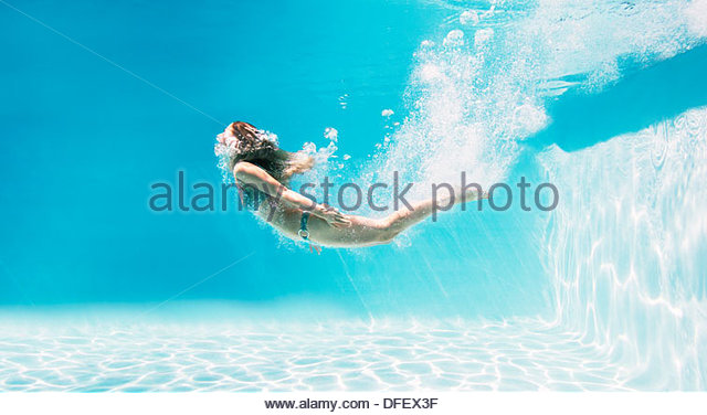 Woman swimming underwater in swimming pool - Stock Image