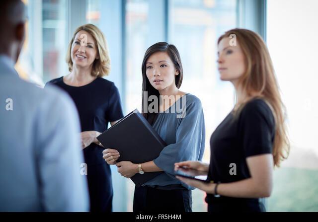 Attentive businesswomen listening to businessman - Stock-Bilder