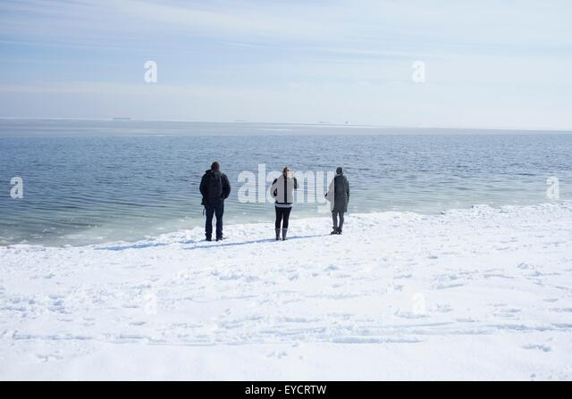 Three adults looking out to sea, Fairfield, Connecticut, USA - Stock Image