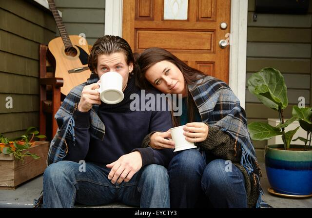 Young couple on porch step wrapped in blanket drinking coffee - Stock Image