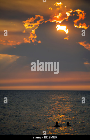 Two swimmers in the water enjoying a magnificent sunset over Holbox Island, Quintana Roo, Yucatán Peninsula, - Stock Image