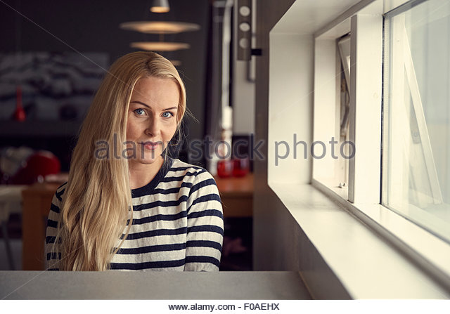 Portrait of woman with long blond hair sitting at kitchen breakfast bar - Stock Image