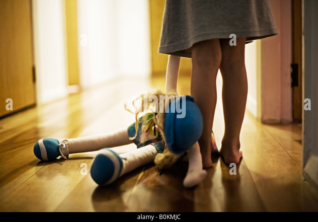 Girl aged four carries toy doll in hall - Stock-Bilder