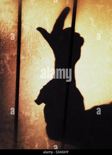 A man casting a shadow on a wall, counting on his hand. Number two. - Stock Image