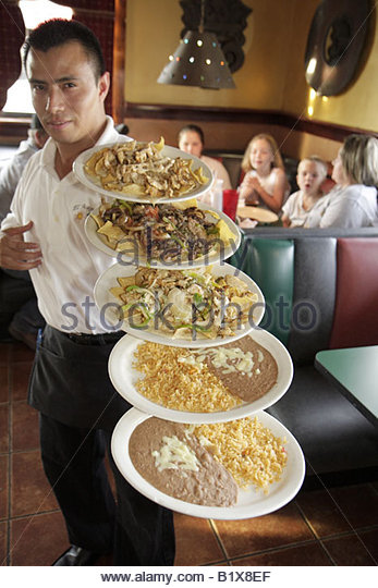 Arkansas Pocahontas El Acapulco Authentic Mexican Cuisine restaurant Hispanic man waiter balance talent plates food - Stock Image