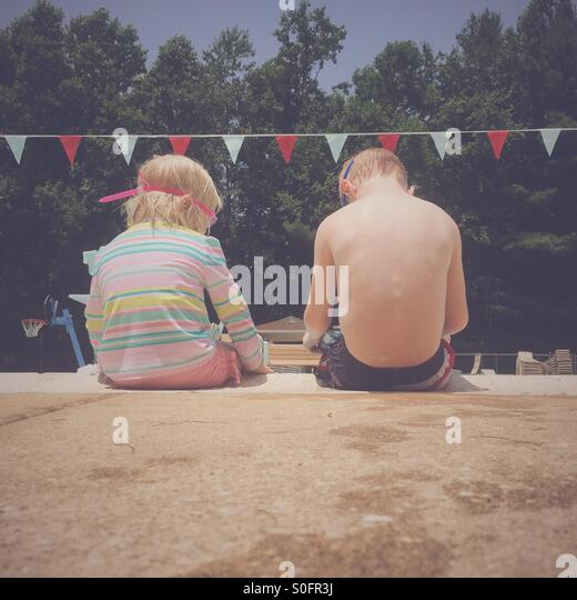 Two young children sitting next to each other on the side of a swimming pool. - Stock Image