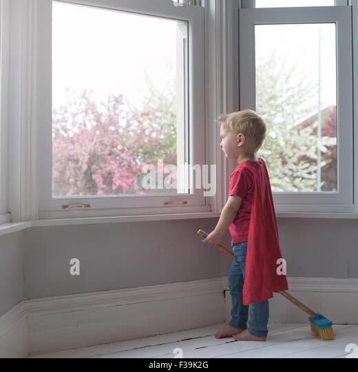 Boy dressed like superhero, looking through window - Stock Image