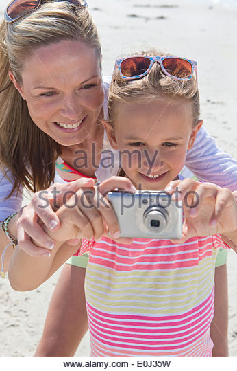 Close up of mother and daughter with digital camera on sunny beach - Stock Image