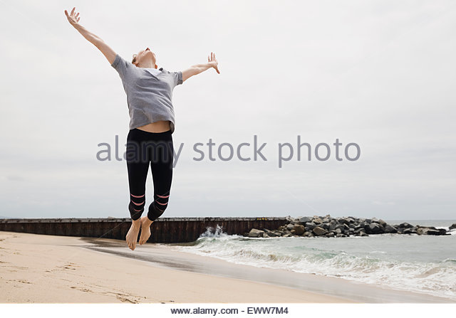 Exuberant woman jumping for joy on beach - Stock Image