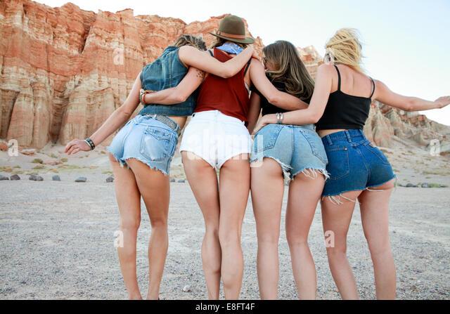 Rear view of four women wearing denim shorts - Stock Image