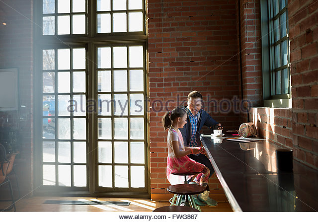 Father and daughter enjoying coffee in coffee shop - Stock Image