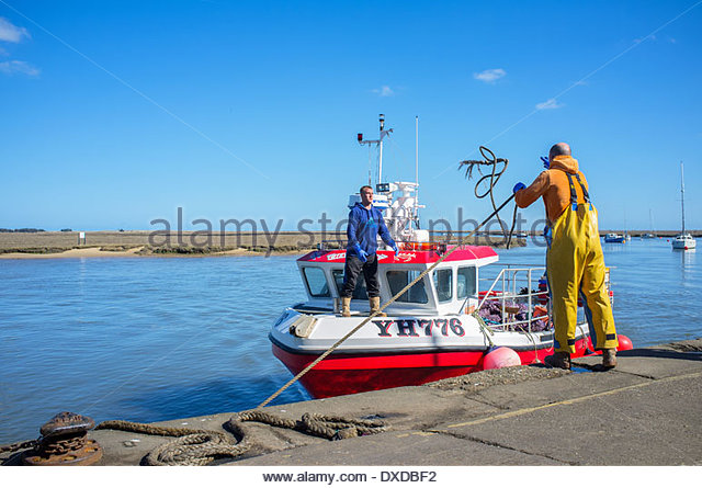 A fishing trawler returns home on a sunny day to it's port of Wells-Next-The-Sea on the North Norfolk Coast - Stock-Bilder