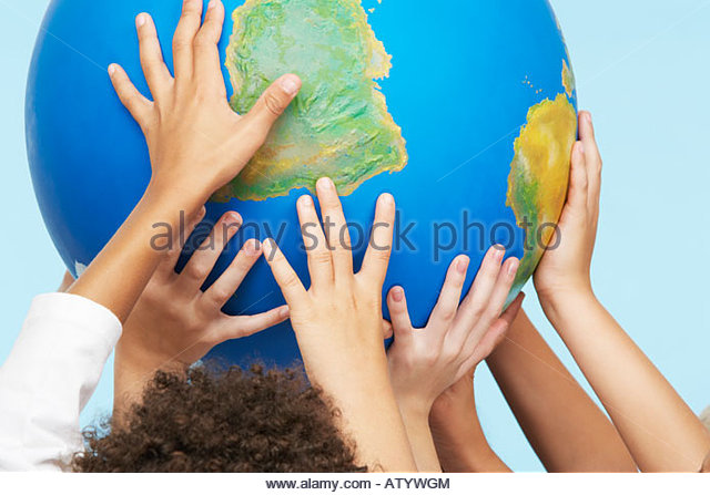 Five children's hands indoors touching a globe - Stock Image