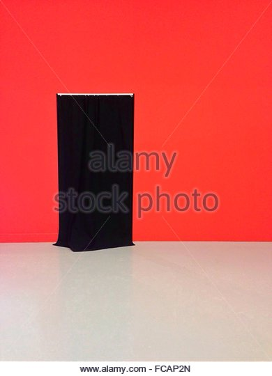 Black Curtain At Entrance On Red Wall - Stock Image