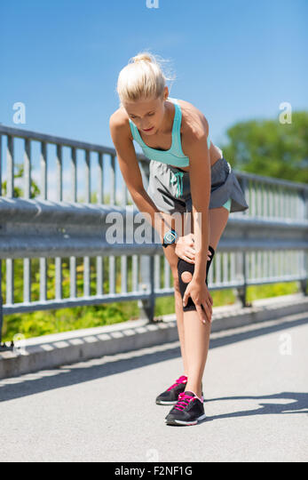young woman with injured knee or leg outdoors - Stock-Bilder