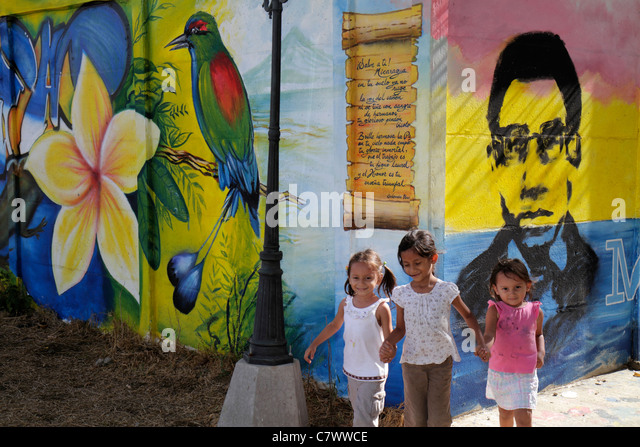 Managua Nicaragua Calle Colon public art mural colorful bird flower person Hispanic girl child younger older sibling - Stock Image