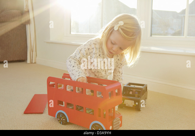 Girl playing with toy bus on floor - Stock Image
