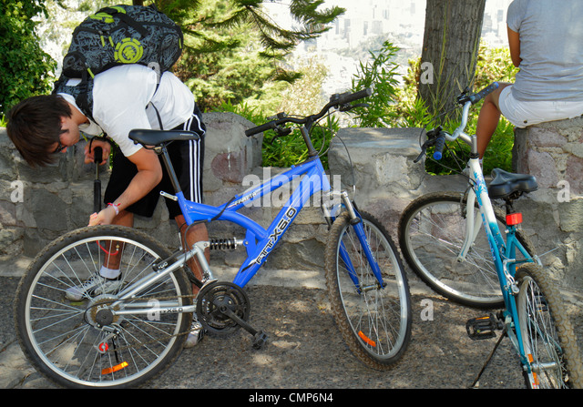 Santiago Chile Cerro San Cristobal Terraza Bellavista overlook Hispanic man cyclist bicycle tire pumping air backpack - Stock Image