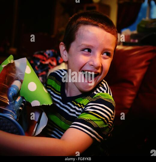 Happy Boy With Mouth Open Holding Gift While Sitting On Sofa At Home - Stock Image
