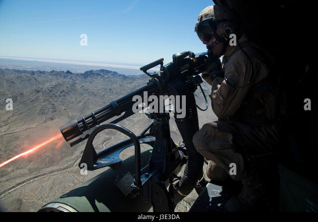 U.S. Marine soldiers operate a GAU-17 Vulcan Gatling machine gun cannon from a USMC UH-1Y Venom helicopter during - Stock Image