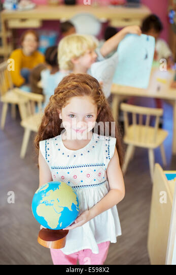 Student holding globe in classroom - Stock Image