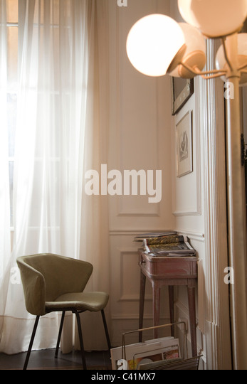 Empty chair and magazine on desk in home interior - Stock Image