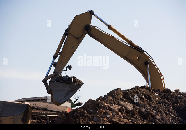 Earth mover and pile of rubble - Stock Image