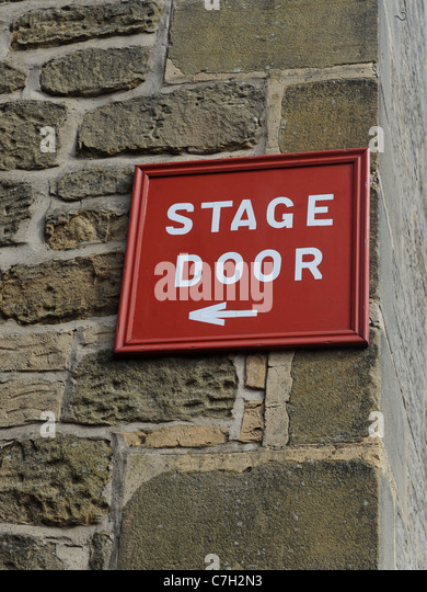 A stage door sign on a brick wall - Stock-Bilder