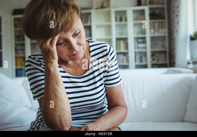 Tense woman sitting on sofa in living room - Stock Image