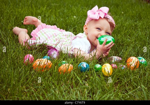 Baby girl laying in the grass with an assortment of colored Easter eggs - Stock Image