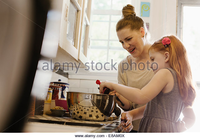 Mid adult mother giving daughter a helping hand in kitchen - Stock Image